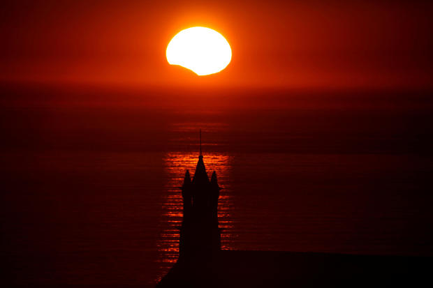 The Saint-They Chapel is seen in silhouette at sunset during a partial solar eclipse as the moon passes in front of the sun seen at the Pointe du Van