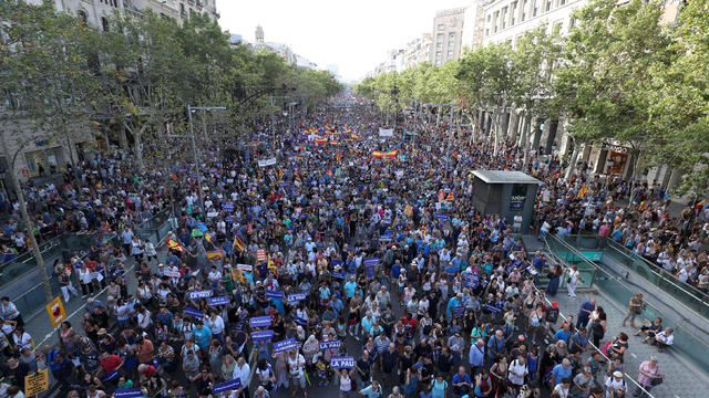 People hold signs and flags as they take part in a march of unity after the attacks last week, in Barcelona, Spain