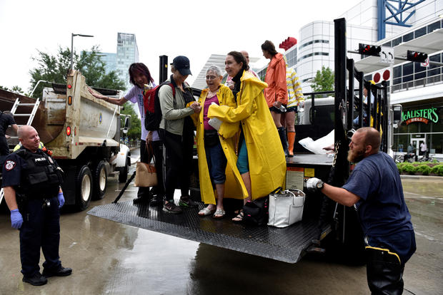 Evacuees are unloaded from the back of an open bed truck at the George R. Brown Convention Center after Hurricane Harvey inundated the Texas Gulf coast with rain causing widespread flooding,