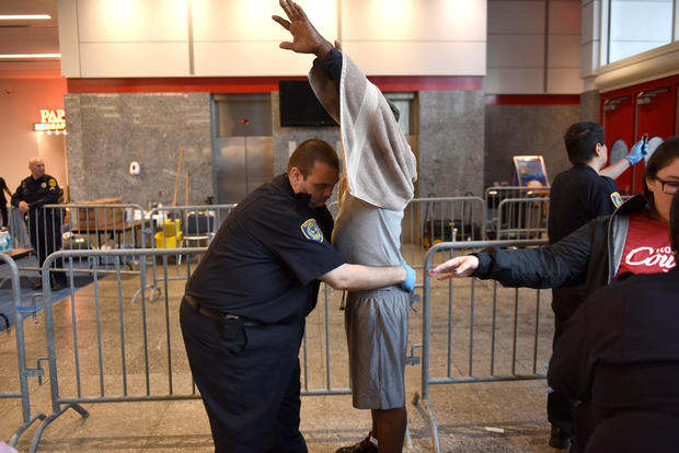 An evacuee is patted down as he is processed into the George R. Brown Convention Center where people have taken refuge, in Houston