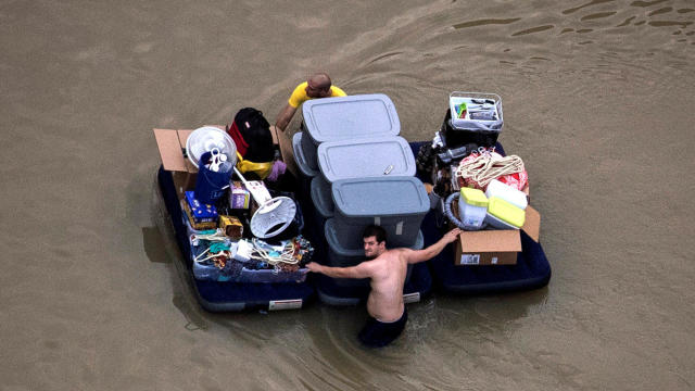 Residents wade with their belongings through floodwaters brought by Tropical Storm Harvey in Houston, Texas, Aug. 30, 2017.