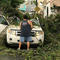 A man removes debris from a car following high winds as Hurricane Irma nears San Juan