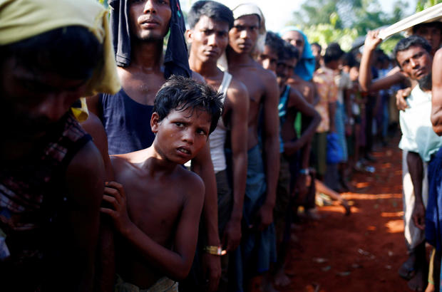 A Rohingya refugee boy looks on as he stands in a queue to receive relief supplies given by local people in Coxís Bazar