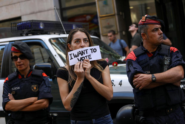 A protestor holds up a sign in front of a Catalan police outside the Catalan region's foreign affairs ministry building during a raid by Spanish police on government offices, in Barcelona
