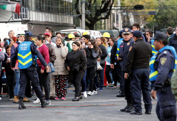 Police officers and people wait along the street after a tremor was felt in Mexico City
