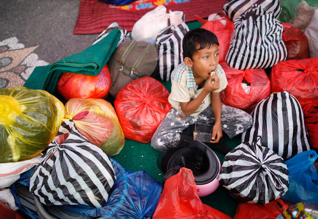 A boy sits amongst his family belongings after he was evacuated from a village located along the slopes of Mount Agung at a temporary shelter in Rendang, Bali