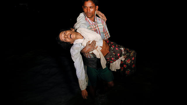 Nobi Hossain wades through the water carrying his elderly relative Sona Banu as hundreds of Rohingya refugees arrive under the cover of darkness by wooden boats from Myanmar to the shore of Shah Porir Dwip