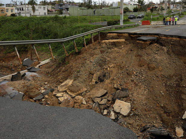 Workers prevent cars from driving down a road washed out during Hurricane Maria in San Sebastian, Puerto Rico