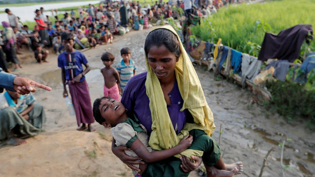 A Rohingya refugee woman who crossed the border from Myanmar a day before, carries her daughter and searches for help as they wait to receive permission from the Bangladeshi army to continue their way to the refugee camps, in Palang Khali