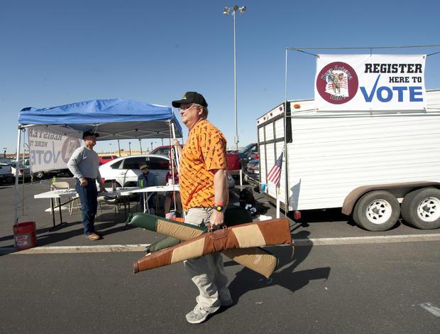A man carries his guns past a voter regi