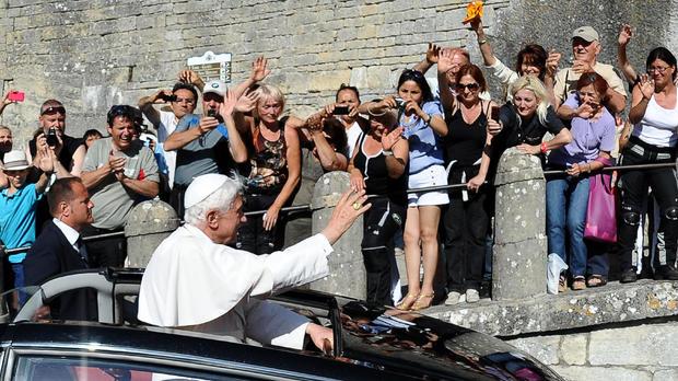 Pope Benedict XVI (C) waves to the faith