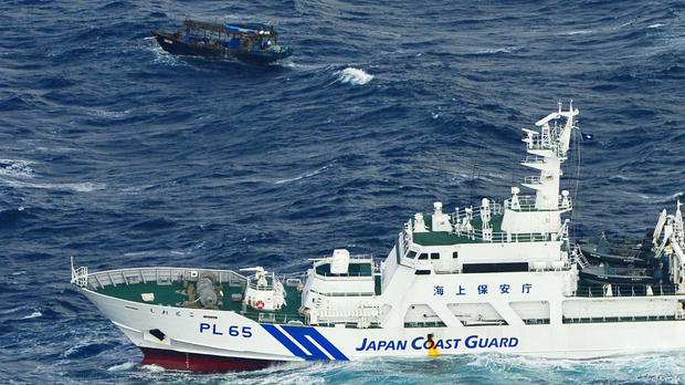 A Japan Coast Guard vessel sails near a drifting wooden boat carrying men identified as North Koreans off Matsumae on the northern Japanese island of Hokkaido, in this photo taken by Kyodo Nov. 29, 2017.