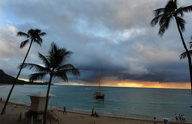 Tourists enjoy a walk at the Waikiki bea