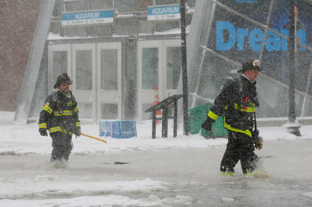Boston firefighters wade through a street flooded from tidal surge during Storm Grayson in Boston