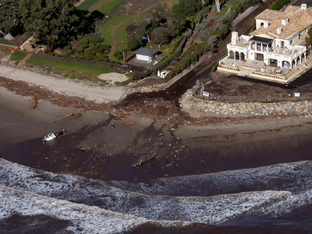 An aerial photo showing two vehicles submerged in the surf amidst debris from a mudslide due to heavy rains in Montecito