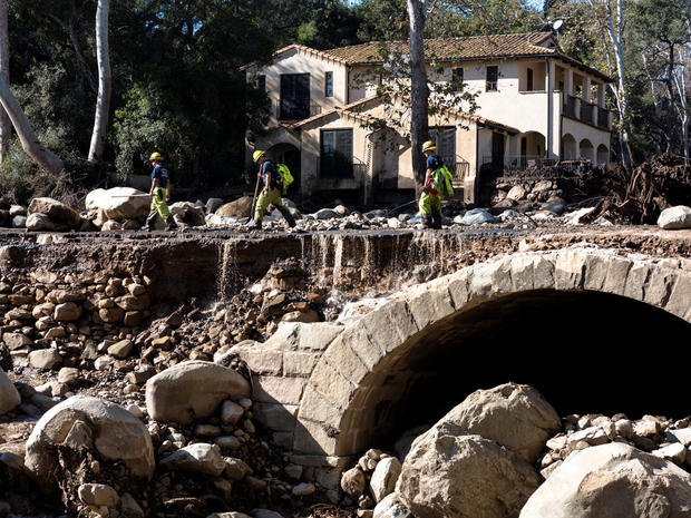 Montecito firefighters walk on a road damaged by mudslides in Montecito, California