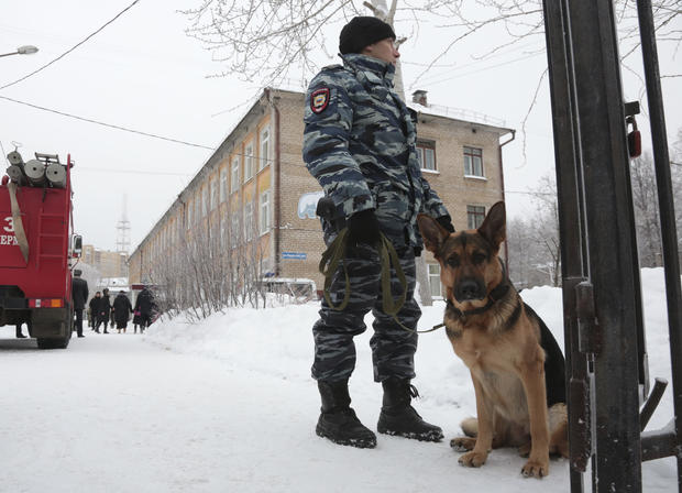 A policeman with a dog stands guard near a local school after reportedly several unidentified people wearing masks injured schoolchildren with knives in Perm