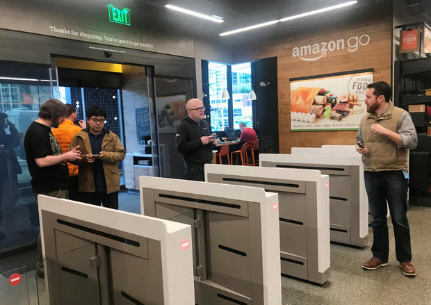 """Shoppers enter the Amazon Go store located in Amazon's """"Day 1"""" office building in Seattle"""