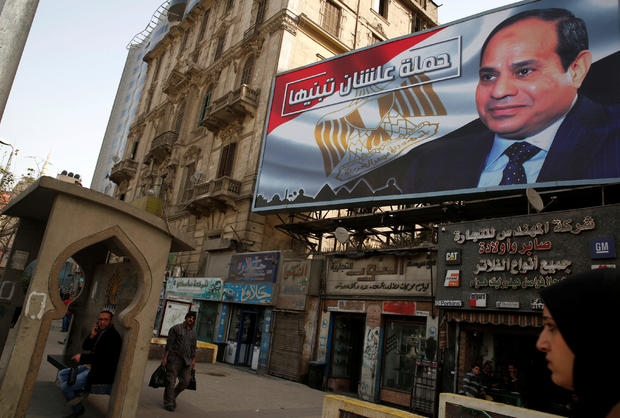 """People walk by a poster of Egypt's President Abdel Fattah al-Sisi from the campaign titled """"Alashan Tabneeha"""" (So You Can Build It), for the upcoming presidential election in Cairo"""