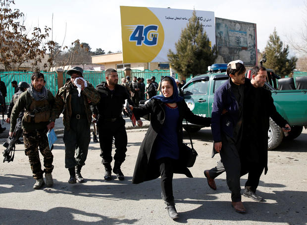 Afghan security forces members and civilians assist the injured after a blast in Kabul