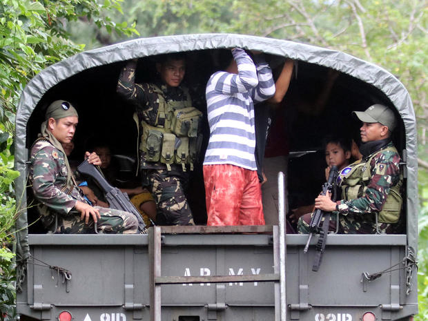 Soldiers and residents are seen on a military truck departing to evacuation centers after Mayon volcano erupted anew, in Padang town