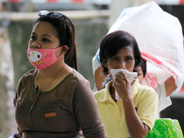 A resident wearing a face mask waits for relief goods after Mayon Volcano erupted at Camalig