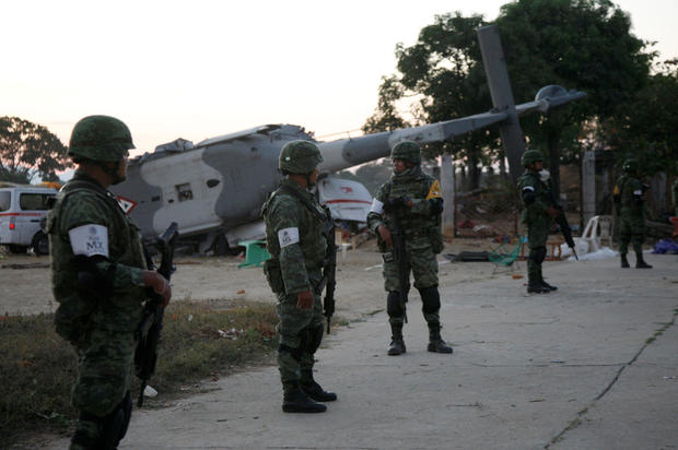 Soldiers stand guard next to a military helicopter, carrying Mexico's interior minister and the governor of the southern state of Oaxaca, crashed on top of two vans in an open field while trying to land in Santiago Jamiltepec