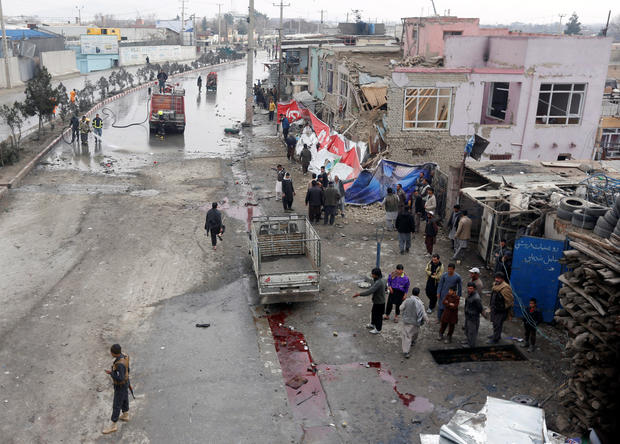 Afghan police inspect the site of a suicide bomb attack in Kabul
