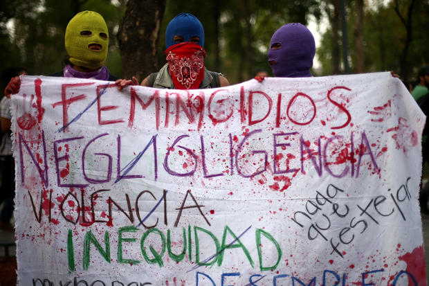Hooded women hold a banner during a demonstration on International Women's Day in Mexico City