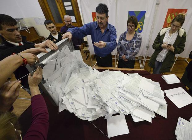 Members of a local election commission empty a ballot box before starting to count votes during the presidential election in Vladivostok