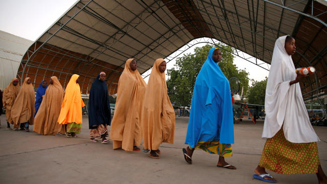 Some of the newly-released Dapchi schoolgirls walk to board a plane in Maiduguri