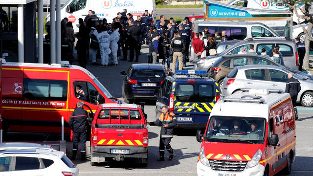 A general view shows rescue forces and police officers at a supermarket after a hostage situation in Trebes