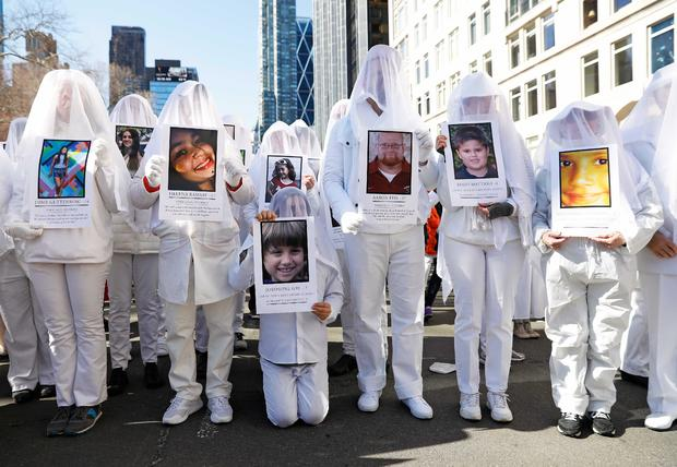 """Protesters hold photos of victims of school shootings during a """"March For Our Lives"""" demonstration demanding gun control in New York City"""