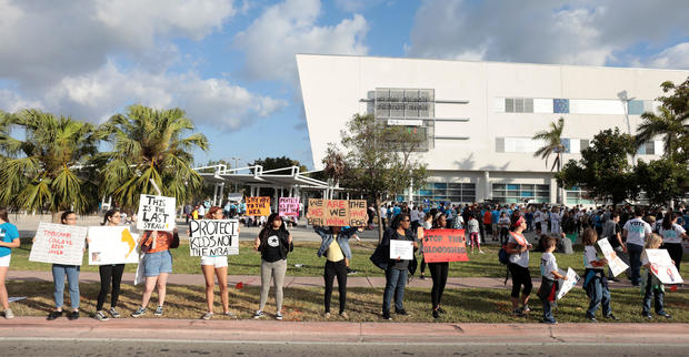 """People hold signs while rallying in the street during """"March for Our Lives"""" in Miami"""