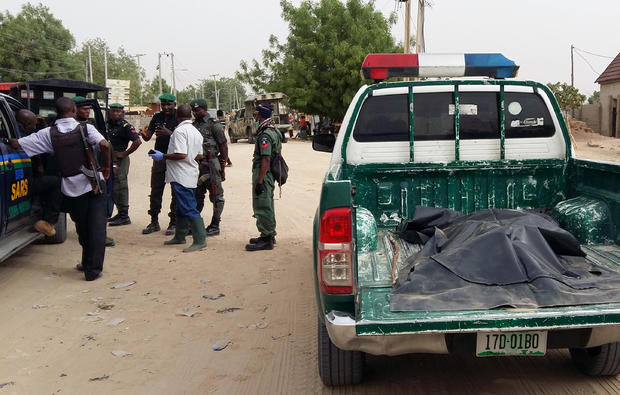 A covered-up dead body lies in the trunk of a police vehicle as members of security forces stand near the site of a suspected Boko Haram attack on the edge of Maiduguri's inner city