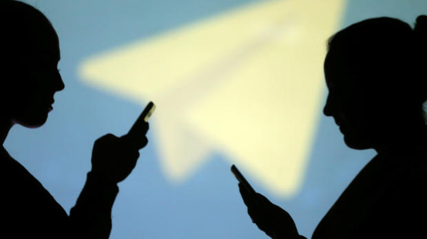 Silhouettes of mobile users are seen next to a screen projection of the Telegram logo in this picture illustration taken March 28, 2018.