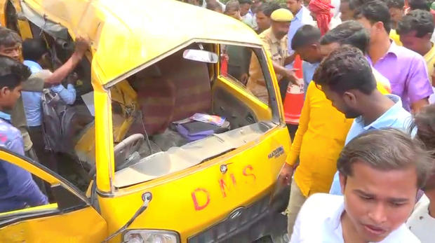 People gather around a school bus after it collided with a train in Uttar Pradesh