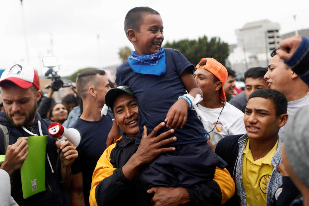 A man and his son, members of a caravan of migrants from Central America, react near the San Ysidro checkpoint as the first fellow migrants entered U.S. territory to seek asylum on Monday, in Tijuana