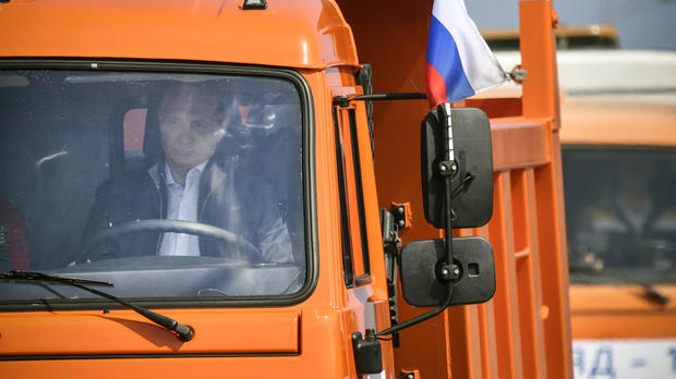 Russian President Vladimir Putin drives a Kamaz truck during a ceremony opening a bridge to connect the Russian mainland with the Crimean peninsula across the Kerch Strait, May 15, 2018.