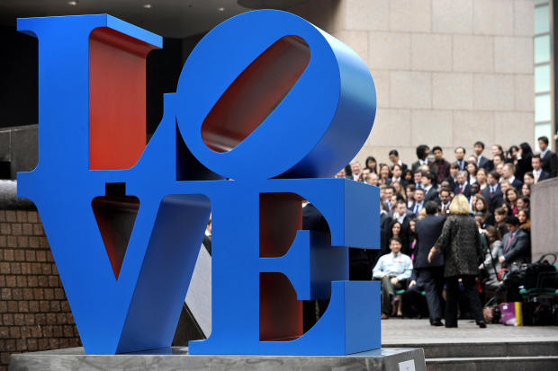 """A sculpture by artist Robert Indiana is displayed in a public area in Hong Kong on March 9, 2008, as people gather for a group photo. The sculpture is inspired from Indiana's """"Love"""" painting from the 1960s."""