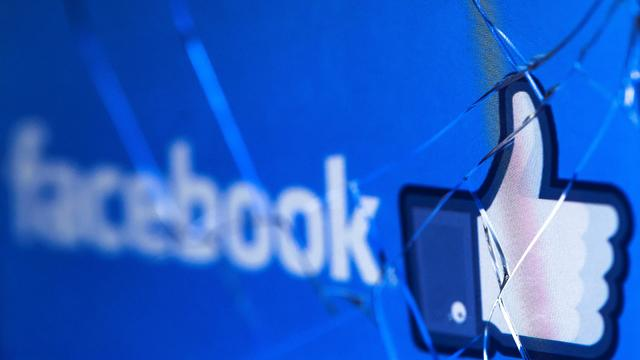Facebook logo on broken cracked mobile phone screen