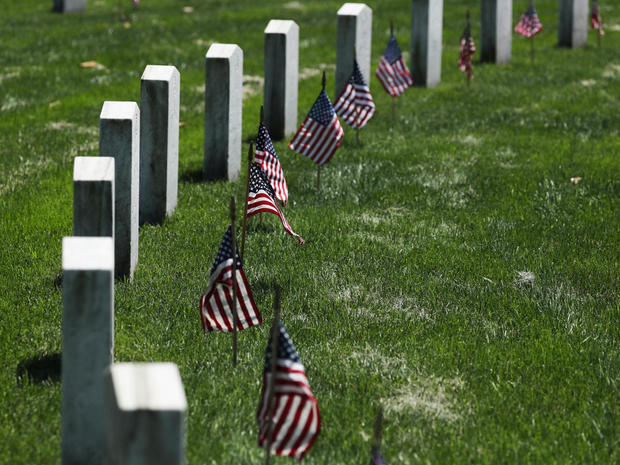 U.S. flags placed by U.S. Army soldiers of the 3rd United States Infantry Regiment lie on graves at Arlington National Cemetery