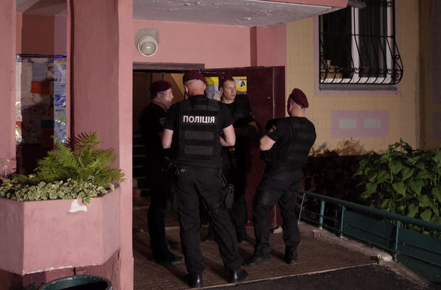 Ukrainian police officers guard in the entrance to a house where Russian journalist Babchenko was shot and died of his wounds in an ambulance, in Kiev