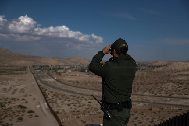 Border patrol agent uses binoculars to search for illegal immigrants along U.S. border with Mexico in Sunland Park, New Mexico,