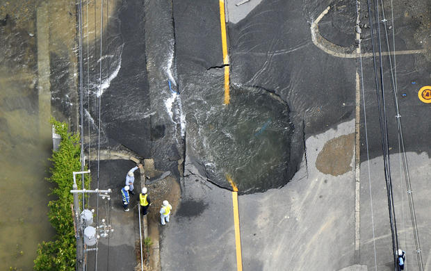 Water flows out from cracks in a road damaged by an earthquake in Takatsuki