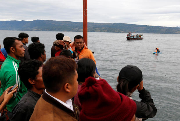 Local residents and relatives of missing passengers from a ferry accident on Lake Toba, wait on the dock at Tigaras Port in Simalungun
