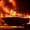 A boat burns as fast-moving wildfire driven by strong wind and high temperatures at the site of a wildfire in Goleta
