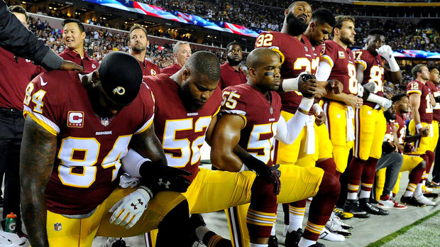 Washington Redskins tight end Niles Paul (84), linebacker Ryan Anderson (52) and linebacker Chris Carter (55) kneel with teammates during the playing of the national anthem before a game against the Oakland Raiders at FedEx Field in Landover, Maryland, on