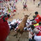 A wild cow leaps over revellers after the seventh running of the bulls of the San Fermin festival in Pamplona