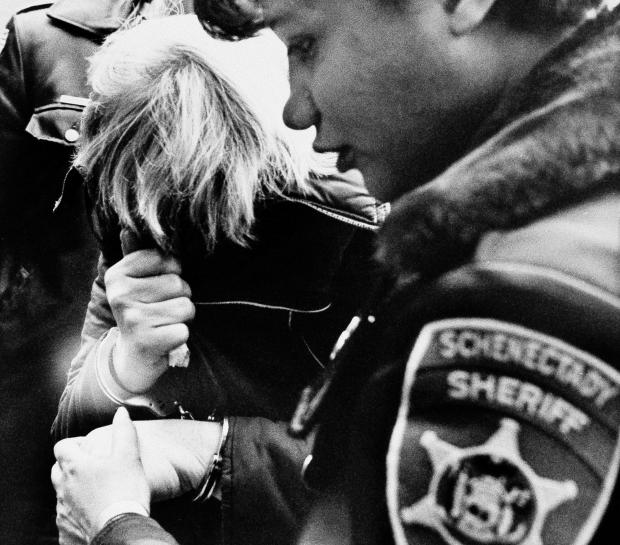 Marybeth Tinning, suspected by Schenectady police of killing the nine children in her care since 1972, covers her face while being escorted by a Schenectady County sheriff's deputy to court for a preliminary hearing on Feb. 11, 1986.